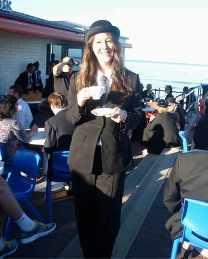 Marianne dressed in suit, bowler hat and tie holding a tea cup and saucer at a surrealist tea party at Henley Beach.